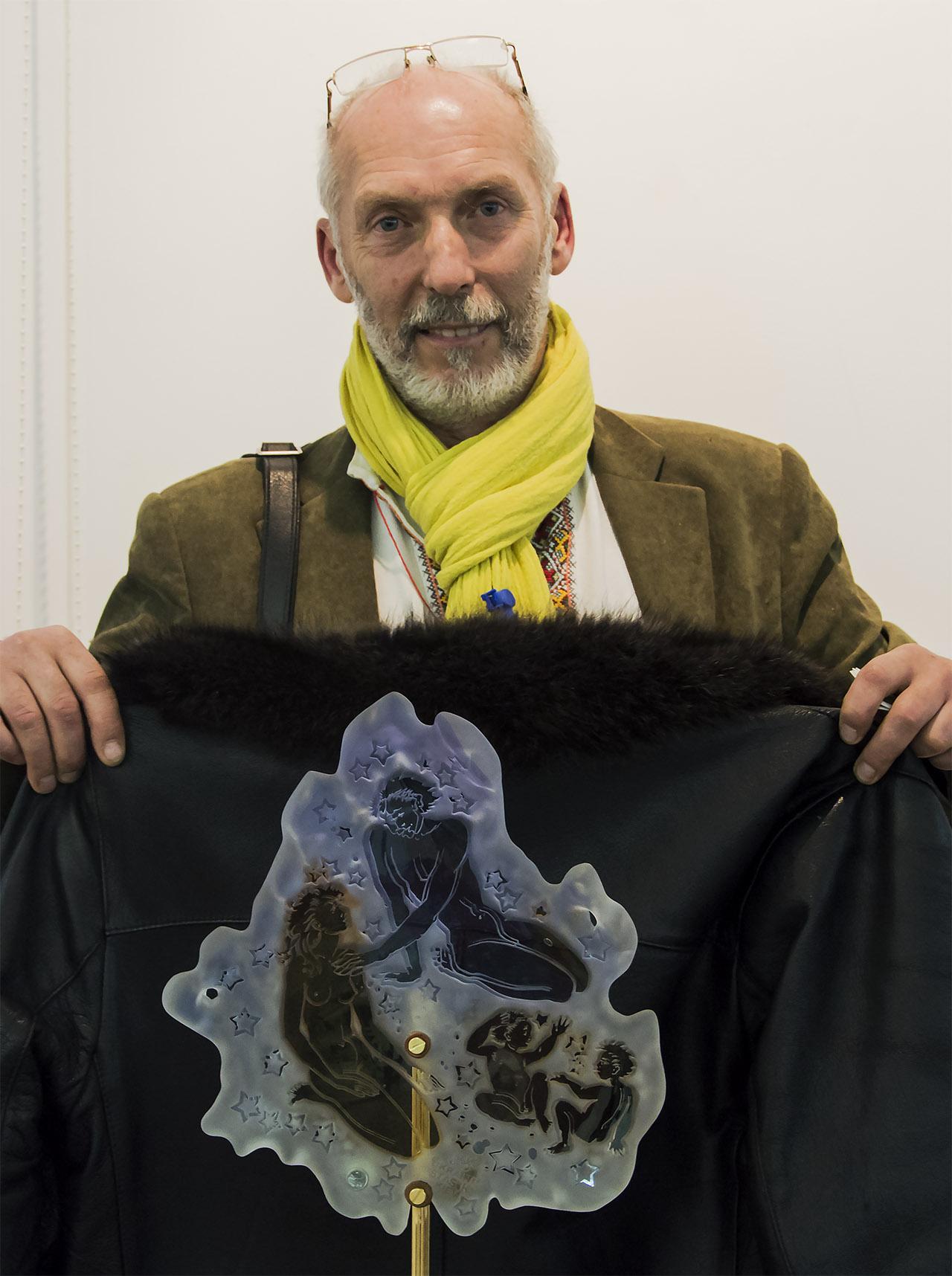 Станіслав Кадочніков демонструє, як виглядатиме його робота на темному тлі. Фото: Ксенія Янко